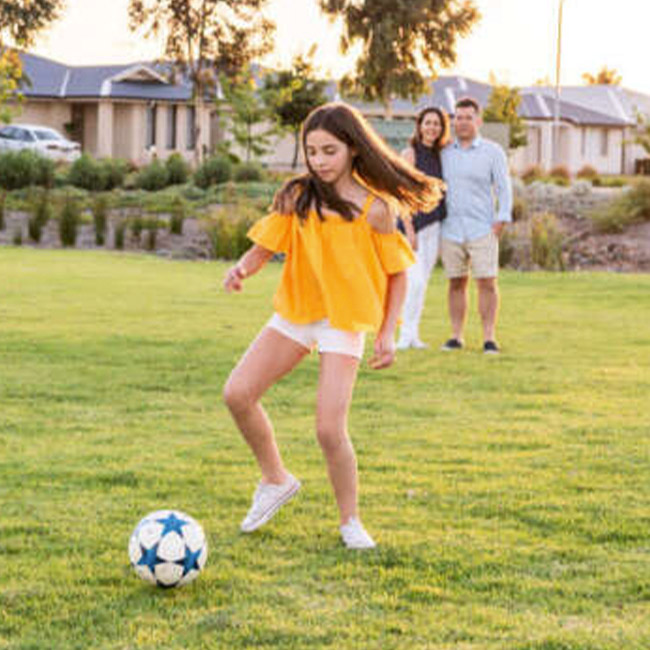 Almond grove estate teen playing soccer in the park