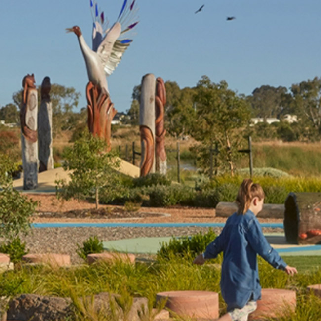 Herpley Estate Park with large bird sculptures in the distance and child playing hopscotch
